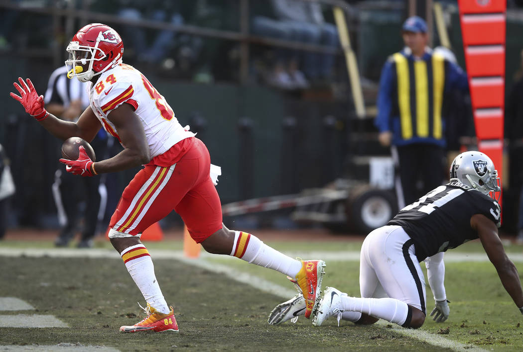 Kansas City Chiefs tight end Demetrius Harris (84) reacts after scoring past Oakland Raiders defensive back Marcus Gilchrist (31) during the second half of an NFL football game in Oakland, Calif., ...