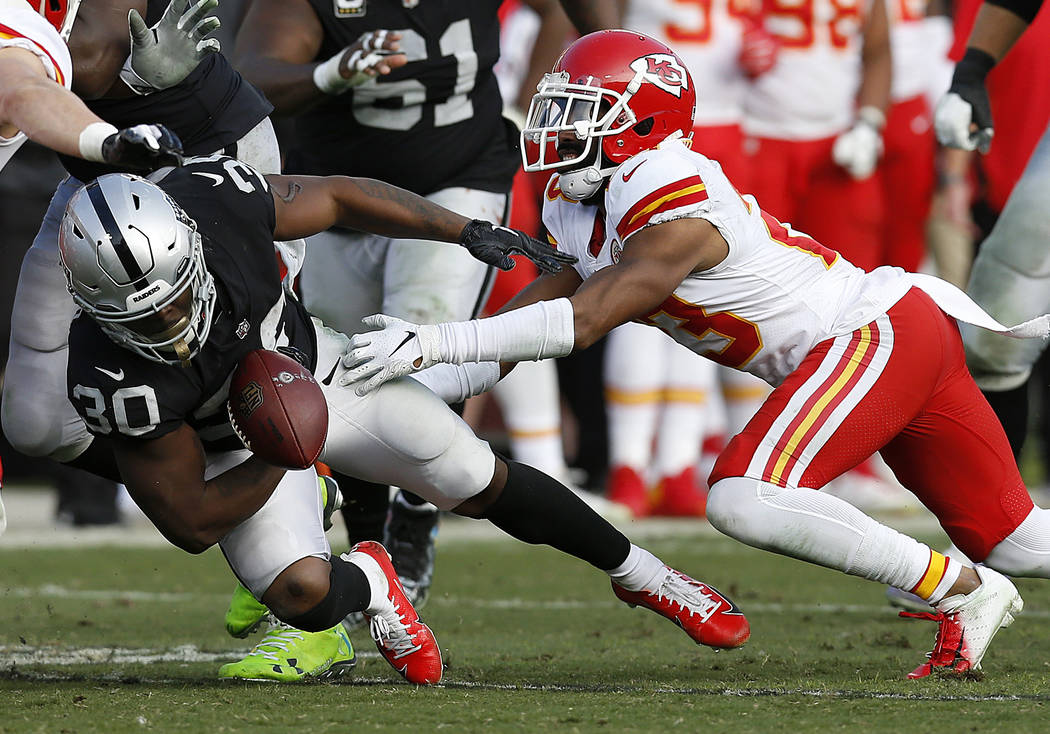 Oakland Raiders running back Jalen Richard (30) fumbles in front of Kansas City Chiefs cornerback Kendall Fuller during the second half of an NFL football game in Oakland, Calif., Sunday, Dec. 2, ...