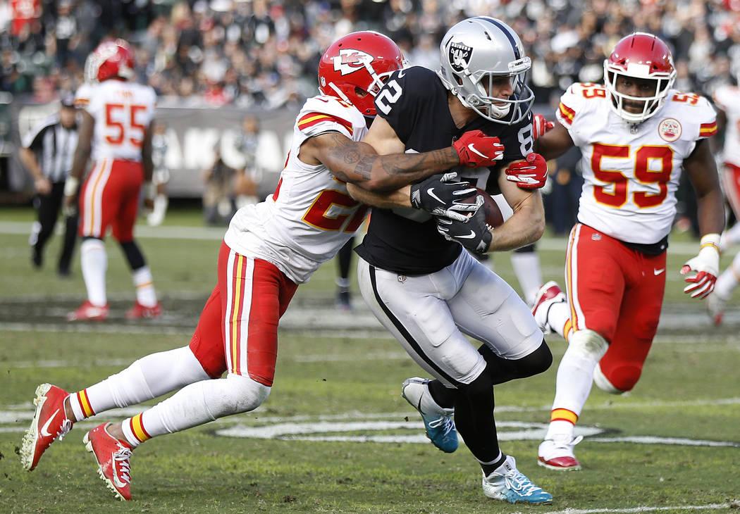 Oakland Raiders wide receiver Jordy Nelson, center, runs against Kansas City Chiefs defensive back Orlando Scandrick, left, and inside linebacker Reggie Ragland (59) during the second half of an N ...