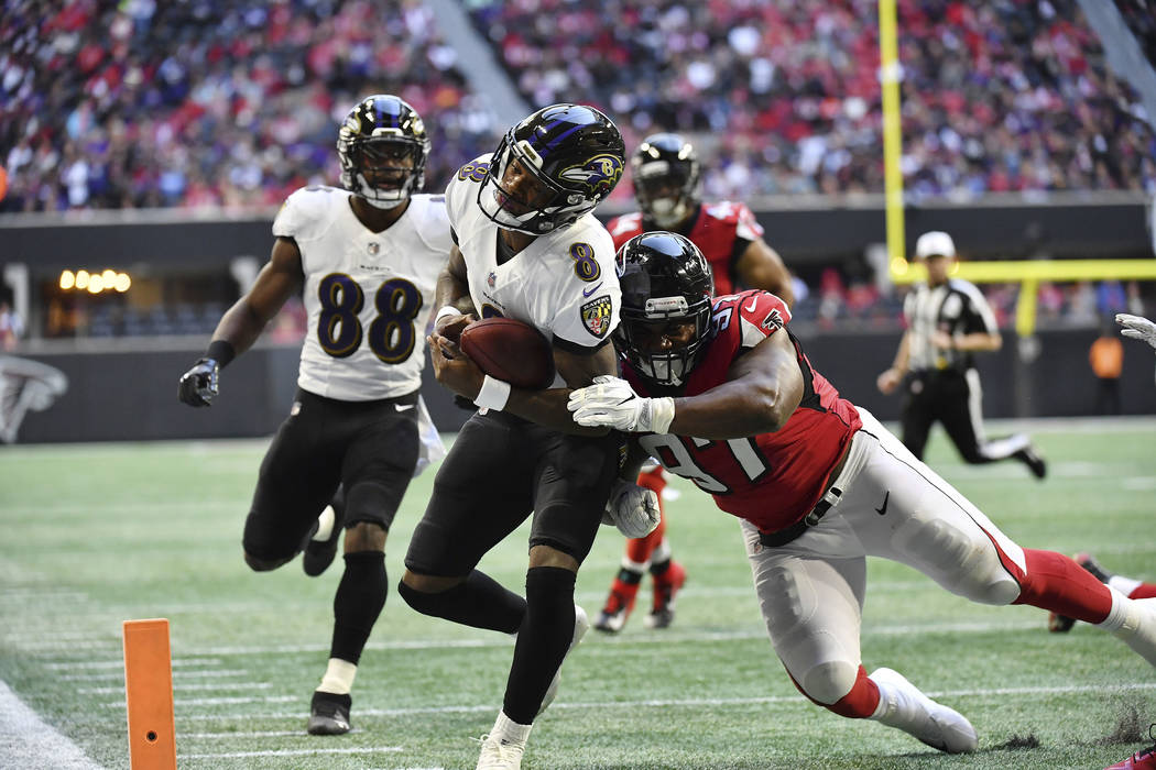 Baltimore Ravens quarterback Lamar Jackson (8) runs into the end zone for a touchdown against Atlanta Falcons defensive tackle Grady Jarrett (97) during the first half of an NFL football game, Sun ...