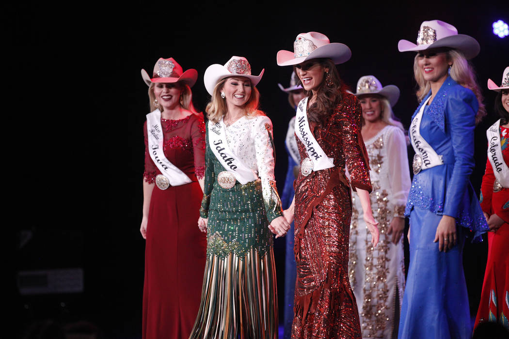 The final five contestants hold hands as they are announced at the Miss Rodeo America 2019 at the Tropicana hotel-casino in Las Vegas, Sunday, Dec. 9, 2018. Sunday was the final day of the more th ...