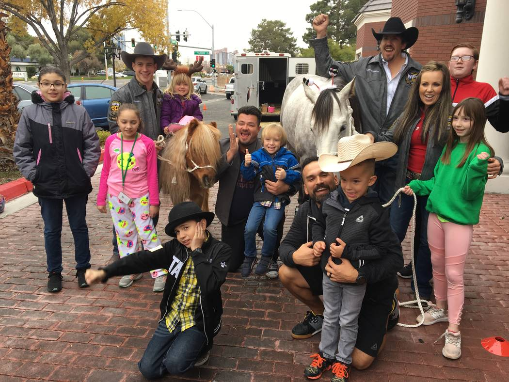 Wrangler NFR contestants Tim O'Connell and Tyler Pearson, left to right in back row donning cowboy hats, gather for a group shot with children and parents during a visit to the Grant a Gift Autism ...