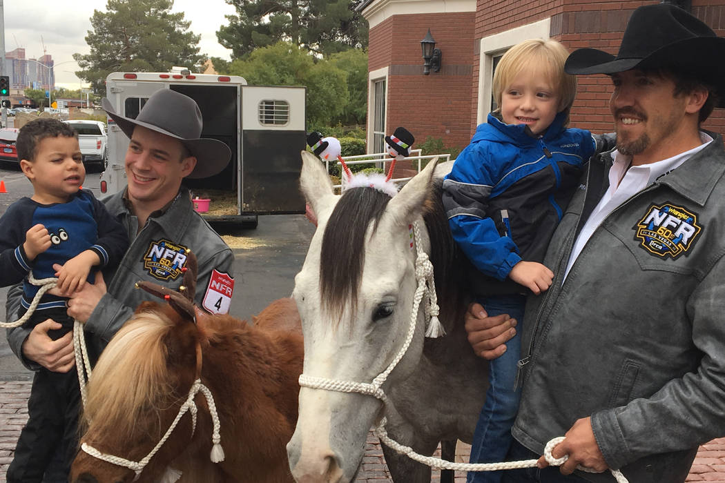 World champion cowboys Tim O'Connell, left, and Tyler Pearson, right, help introduce a couple of youngsters to horses on Friday during a visit to the Grant a Gift Autism Foundation, an event that ...