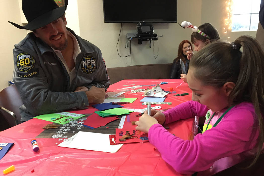 World champion steer wrestler Tyler Pearson, left, smiles approvingly while working with Brazil Calderon on Christmas cards at the Grant a Gift Autism Foundation on Friday afternoon. Wrangler NFR ...