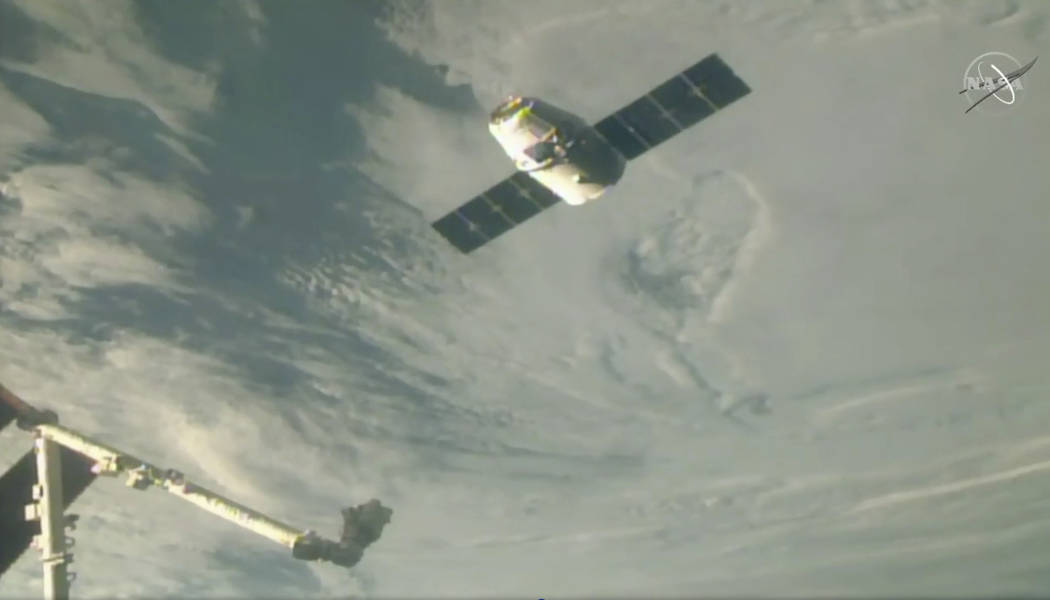 In this image taken from NASA Television, the SpaceX Dragon cargo spacecraft approaches the robotic arm for docking to the International Space Station, Saturday, Dec. 8, 2018. A communication drop ...
