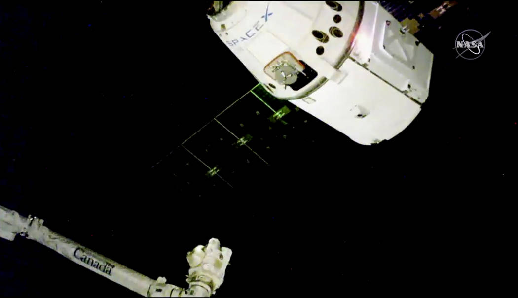 In this image taken from NASA Television, the SpaceX Dragon cargo spacecraft approaches the robotic arm for docking to the International Space Station, Saturday, Dec. 8, 2018. SpaceX delivery ful ...