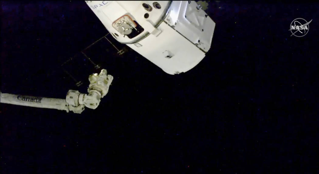 In this image taken from NASA Television, the SpaceX Dragon cargo spacecraft approaches robotic arm for docking to the International Space Station, Saturday, Dec. 8, 2018. A SpaceX delivery full o ...