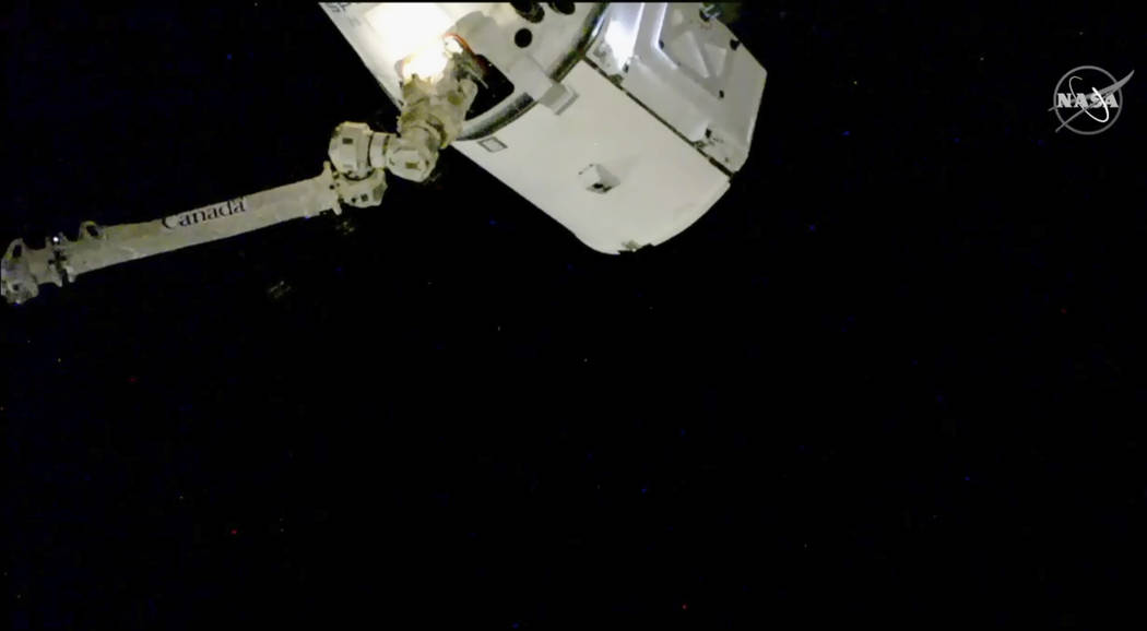 In this image taken from NASA Television, the SpaceX Dragon cargo spacecraft is captured by a robotic arm for docking to the International Space Station, Saturday, Dec. 8, 2018. A SpaceX delivery ...