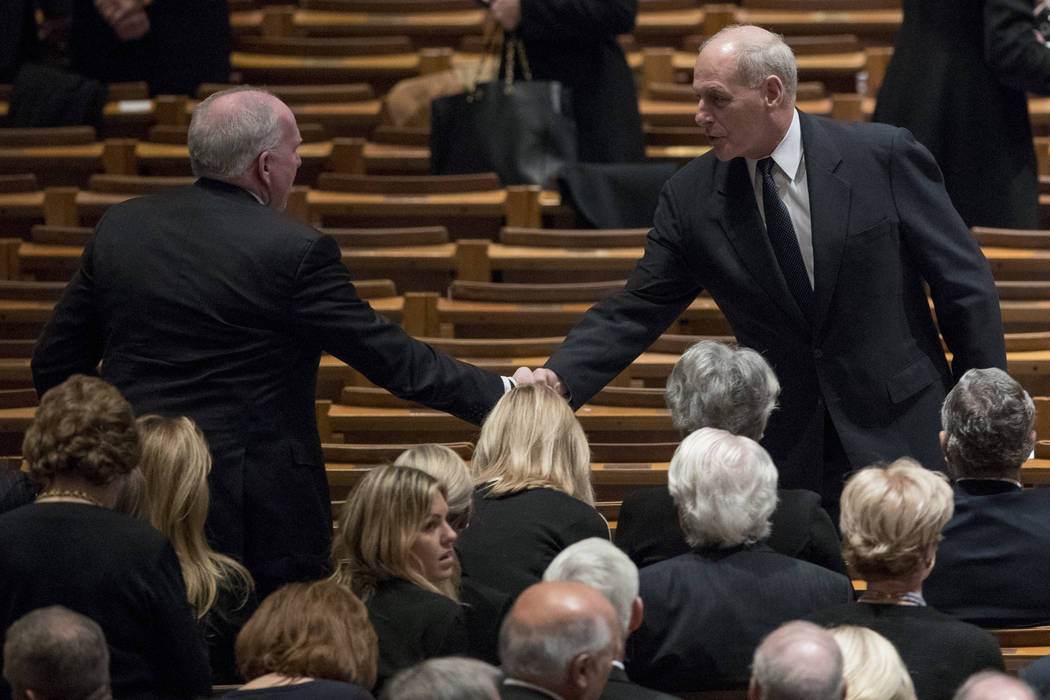 Former CIA Director John Brennan, left, shakes hands with President Donald Trump's Chief of Staff John Kelly, right, before a State Funeral for former President George H.W. Bush at the National Ca ...