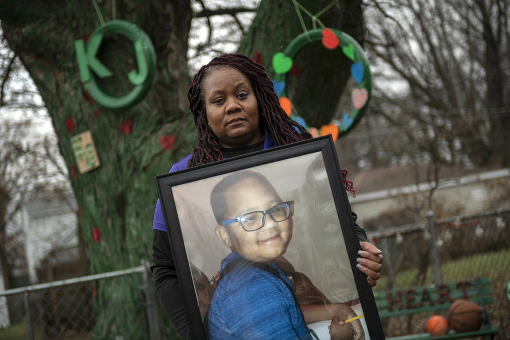 In this Dec. 3, 2018 photo, LaSondra Singleton holds a photo of her son Kenneth Gross Jr. while standing in front of a tree that was decorated in her son's honor at her Warren, Mich., home. Kennet ...