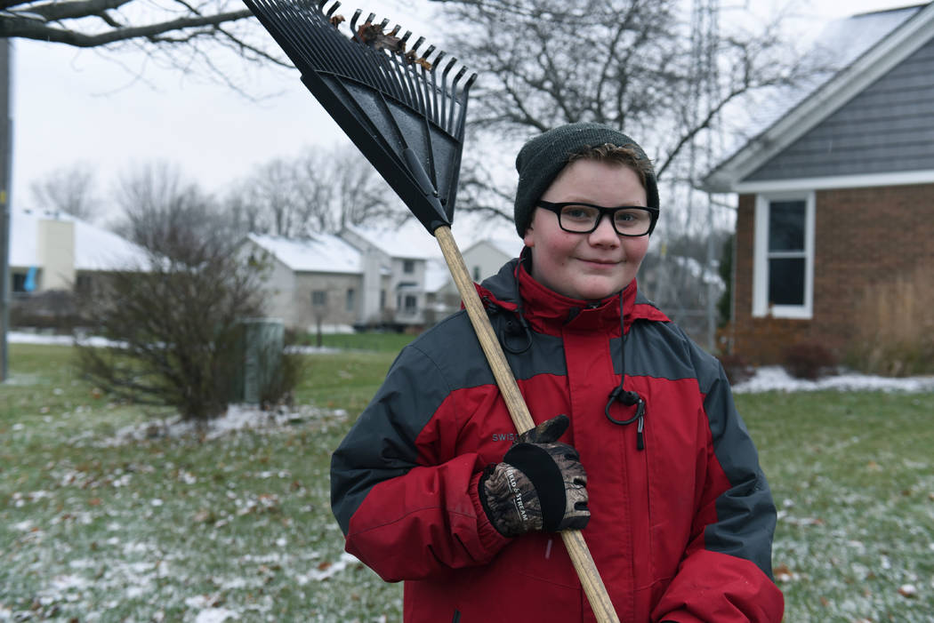 In this Thursday, Nov. 29, 2018 photo, Kaleb Klakulak takes a break from raking leaves outside the home a home in Rochester Hills, Mich., as he raises money for a headstone for his best friend Ken ...