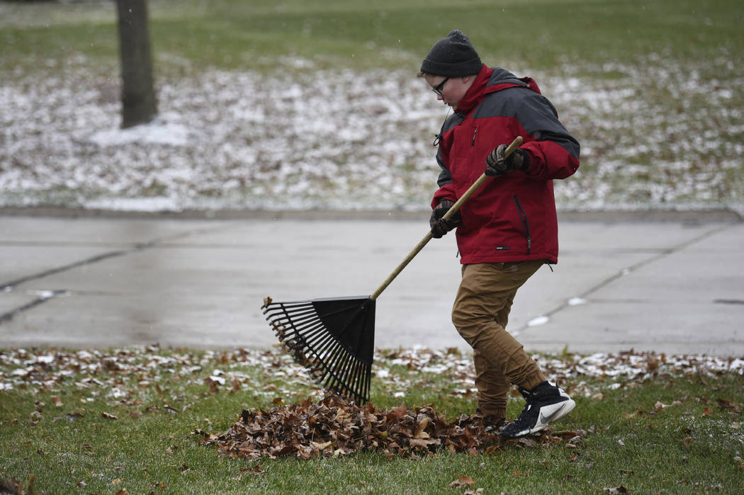 "In this Thursday, Nov. 29, 2018 photo, Kaleb Klakulak rakes leaves in Rochester Hills, Mich., as he raises money for a headstone for his best friend Kenneth ""K.J."" Gross, who died of can ..."