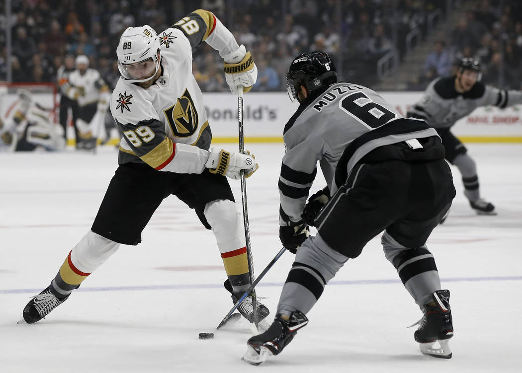 Vegas Golden Knights right wing Alex Tuch, left, battles Los Angeles Kings defenseman Jake Muzzin, right, for the puck during the first period of an NHL hockey game in Los Angeles, Saturday, Dec. ...