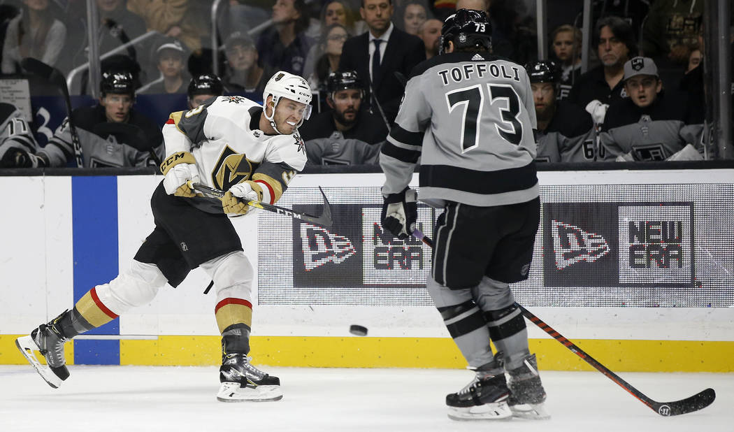 Los Angeles Kings right wing Tyler Toffoli, right, deflects a shot by Vegas Golden Knights defenseman Brayden McNabb, left, during the first period of an NHL hockey game in Los Angeles, Saturday, ...