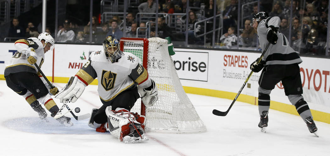 A shot by Los Angeles Kings center Jeff Carter, right, gets deflected into the net by Vegas Golden Knights goaltender Marc-Andre Fleury, center, and defenseman Nate Schmidt, left, for a goal durin ...