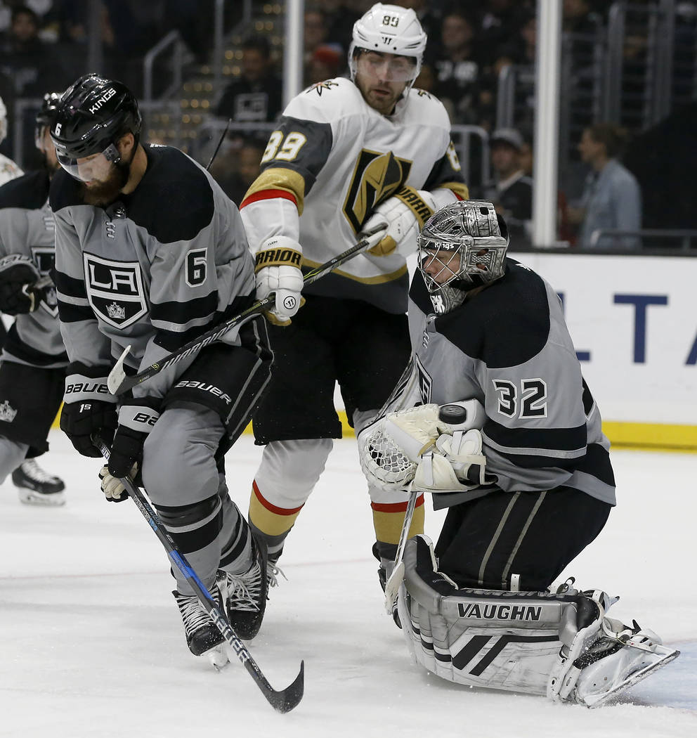 Los Angeles Kings goaltender Jonathan Quick, right, blocks a shot with defenseman Jake Muzzin, left, defending, with Vegas Golden Knights right wing Alex Tuch, center, trying to deflect the puck, ...