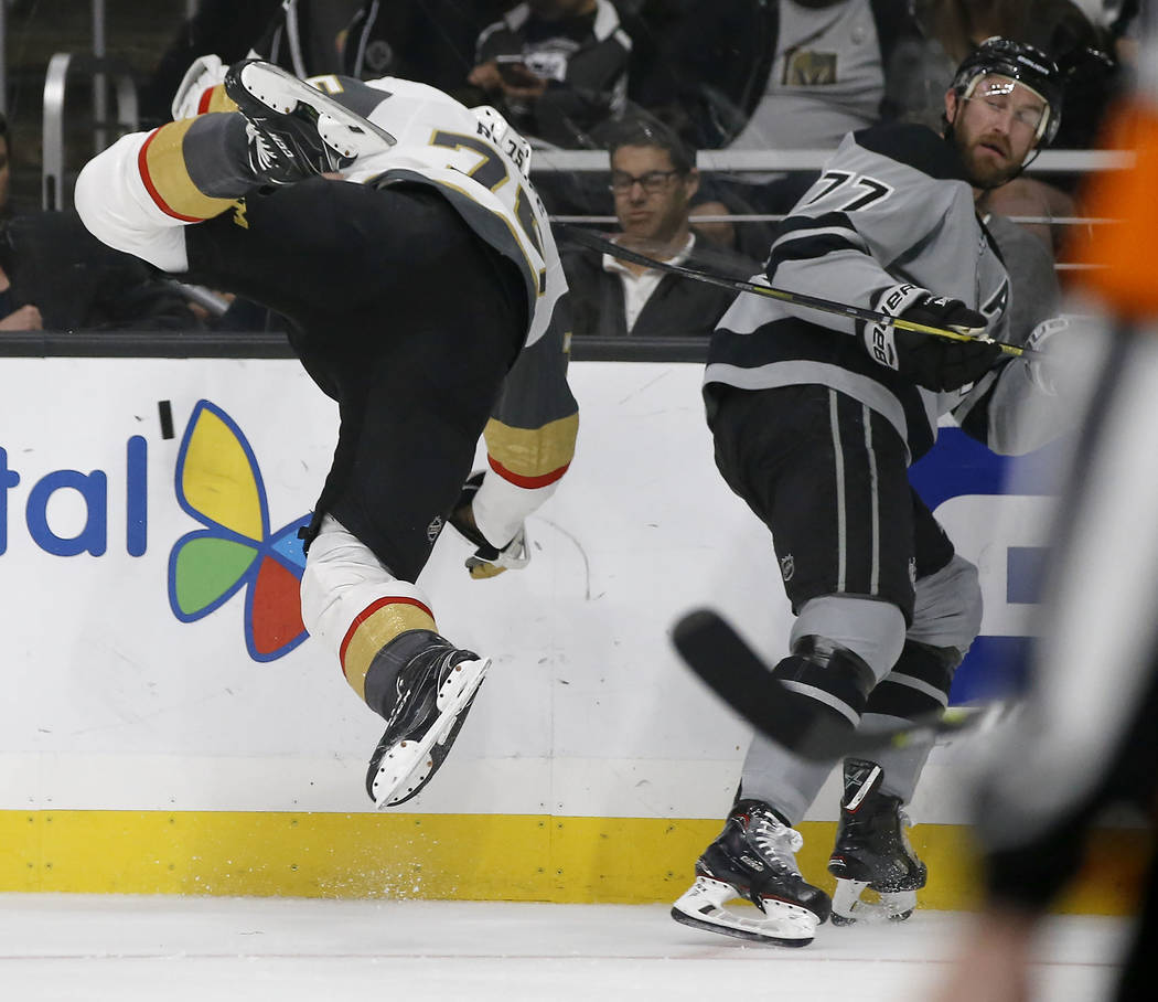 Vegas Golden Knights right wing Ryan Reaves, left, gets airborne after a check by Los Angeles Kings center Jeff Carter, right, during the second period of an NHL hockey game in Los Angeles, Saturd ...