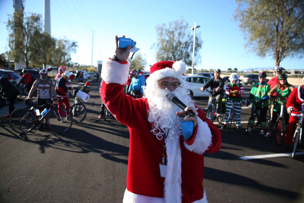 Ron Floth, bicycle outreach coordinator at Regional Transportation Commission of Southern Nevada, dressed as Santa Claus, gives away a bag before the RTC for the Holiday Bike Ride in Las Vegas, Sa ...