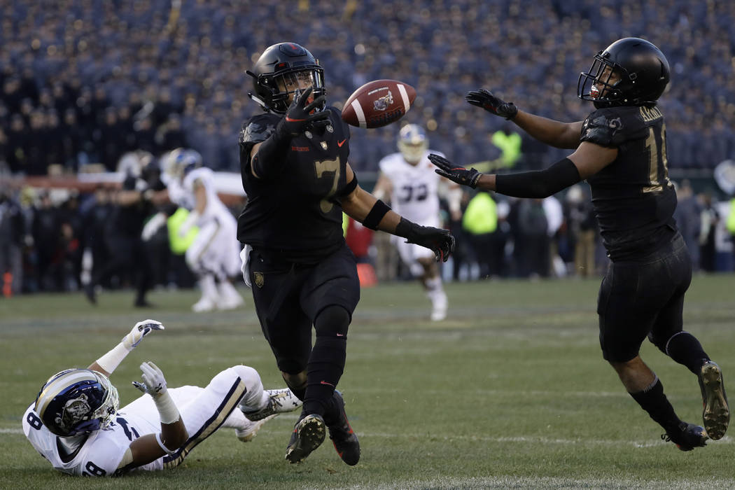 Army's Jaylon McClinton, center, intercepts a pass tipped by teammate Mike Reynolds, right, that was intended for Navy's Mychal Cooper during the first half of an NCAA college football game, Satur ...