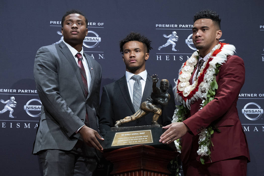 Heisman Trophy finalists, from left, Dwayne Haskins, from Ohio State; Kyler Murray, from Oklahoma; and Tua Tagovailoa, from Alabama, pose with the trophy during a media event Saturday, Dec. 8, 201 ...