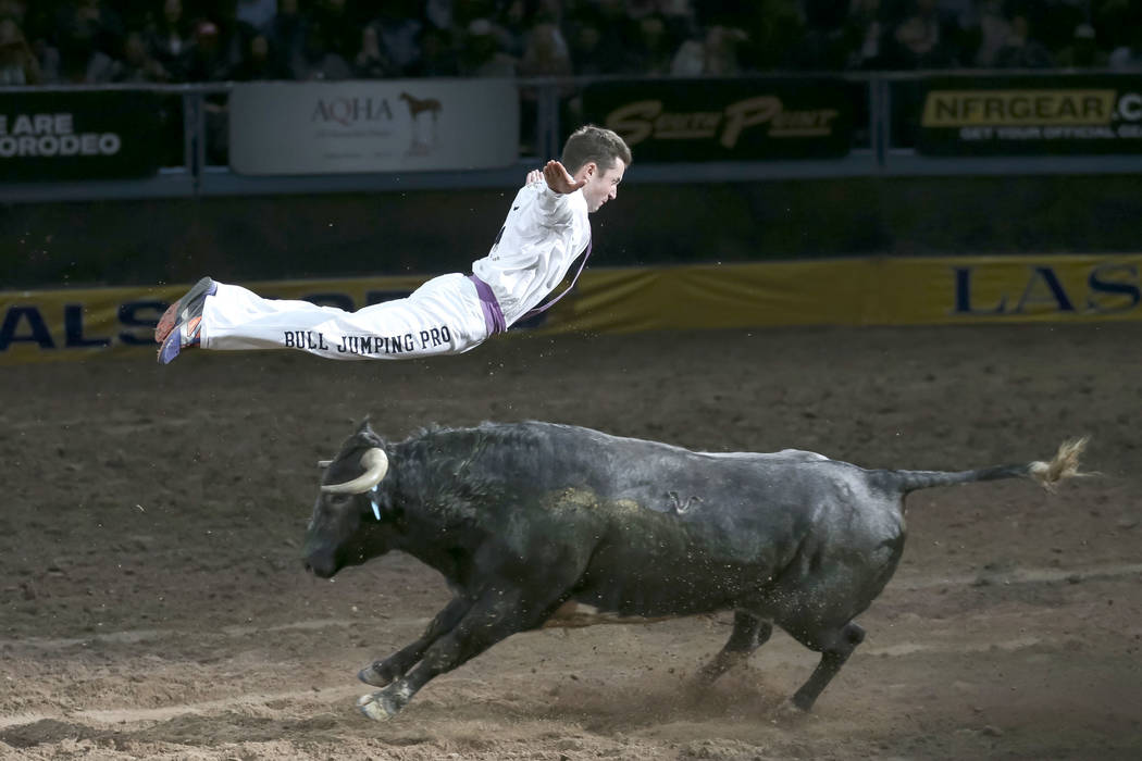 Bull Jumping Pro Emmanuel Lataste leaps over a running bull during a performance on the third go-round of the National Finals Rodeo at the Thomas & Mack Center in Las Vegas on Saturday, Dec. 8 ...