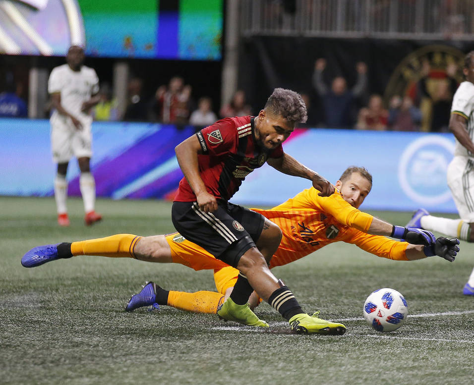 Atlanta United forward Josef Martinez (7) beats Portland Timbers goalkeeper Jeff Attinella (1) to score a goal during the first half of the MLS Cup championship soccer game, Saturday, Dec. 8, 2018 ...