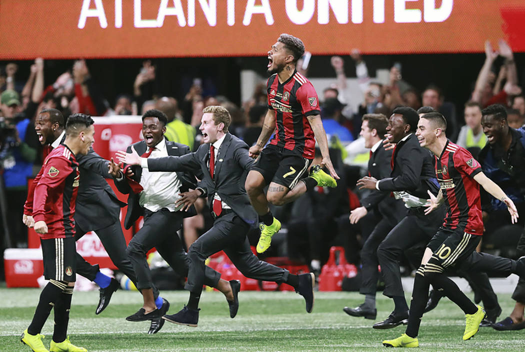 Atlanta United's Josef Martinez (7) leaps in the air and Miguel Almiron (10) charges the field celebrating their 2-0 defeat of the Portland Timbers in the MLS Cup championship soccer game, Saturda ...