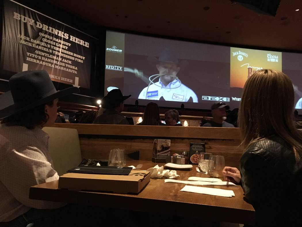 Brandon Noel and Donna Collins of Oakdale, Calif., enjoy Friday night's Wrangler NFR viewing party from a table at California Pizza Kitchen, which is adjacent to the sports book at The Mirage. Pat ...