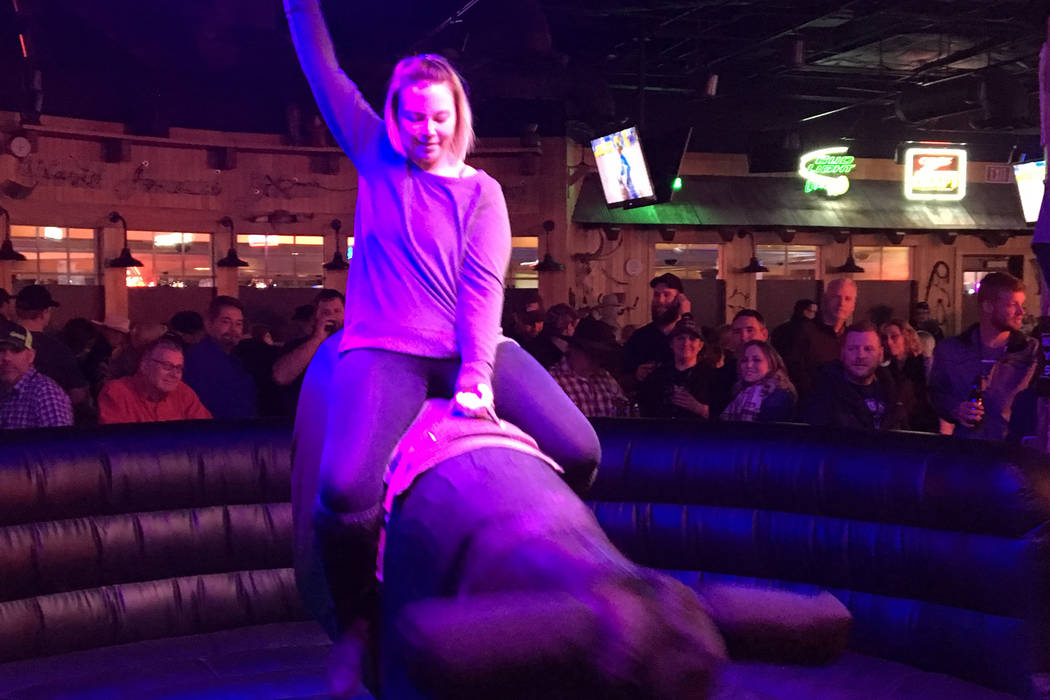 Heather Kizor of Kasota, Minn., takes a ride on the mechanical bull during Friday's Wrangler NFR viewing party at Gilley's Dance Hall & Saloon inside Treasure Island. Patrick Everson/Review-Journal