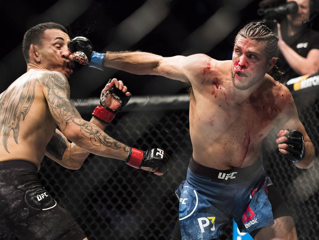 Max Holloway, lefts, take a punch to the face from Brian Ortega during the featherweight championship mixed martial arts bout at UFC 231 in Toronto on Saturday, Dec. 8, 2018. (Nathan Denette/The C ...