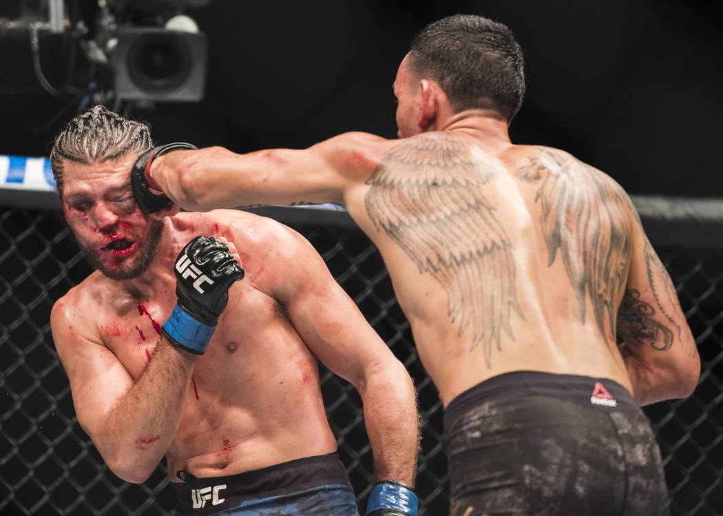 Max Holloway, right, hits Brian Ortega during the featherweight championship mixed martial arts bout at UFC 231 in Toronto on Saturday, Dec. 8, 2018. (Nathan Denette/The Canadian Press via AP)