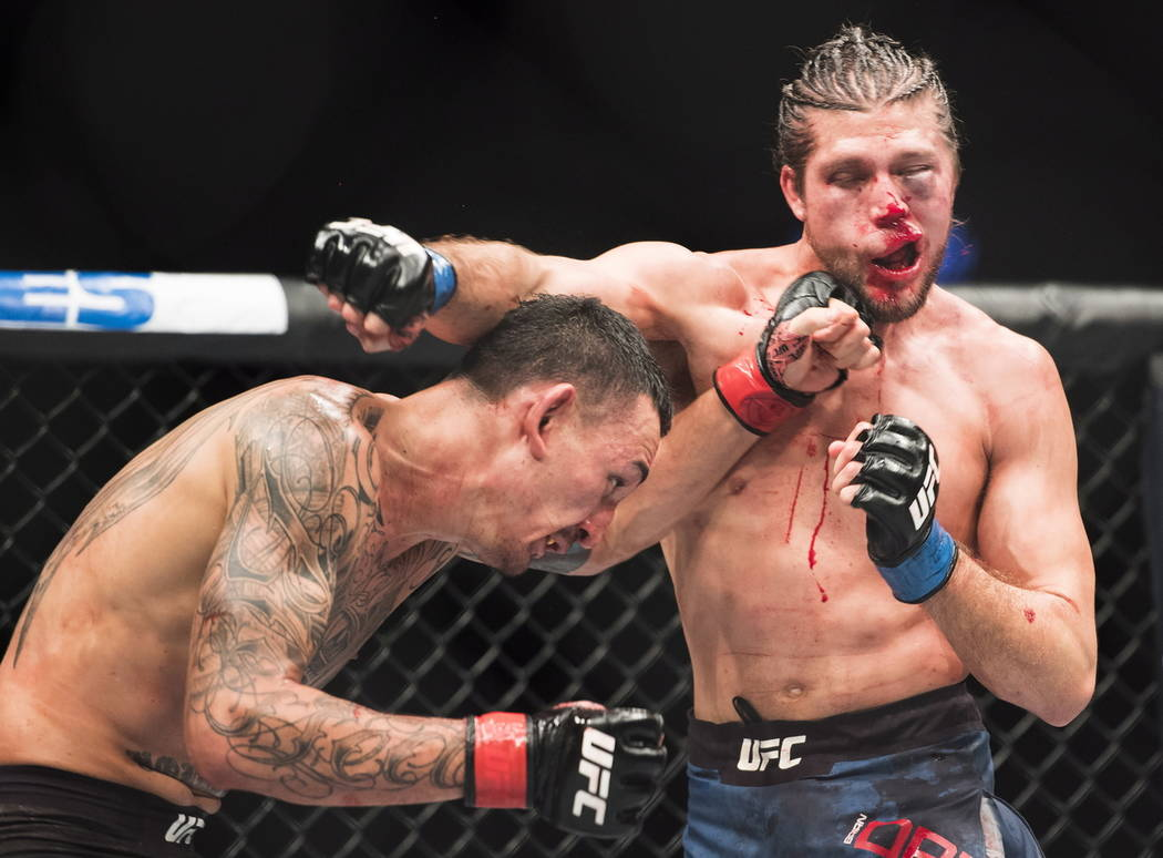Max Holloway, left, fights Brian Ortega during the featherweight championship mixed martial arts bout at UFC 231 in Toronto on Saturday, Dec. 8, 2018. (Nathan Denette/The Canadian Press via AP)