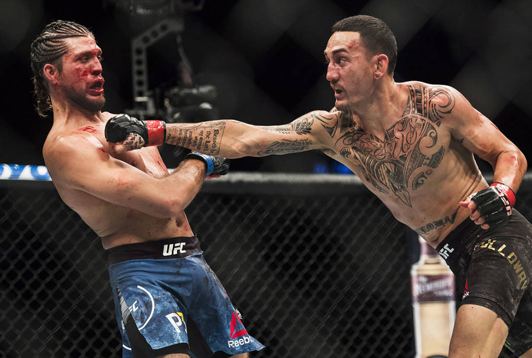 Max Holloway, right, fights Brian Ortega during the UFC Featherweight championship title bout in Toronto on Sunday, Dec. 9, 2018. Holloway won the title fight. (Nathan Denette/The Canadian Press v ...