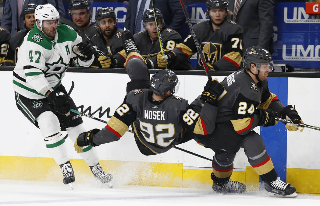 Vegas Golden Knights left wing Tomas Nosek (92) falls to the ice between Dallas Stars right wing Alexander Radulov (47) and center Oscar Lindberg during the second period of an NHL hockey game Sun ...