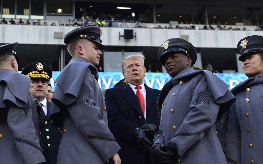 President Donald Trump, center, talks with Army Chief of Staff Gen. Mark Milley, left, watch from the stands before the Army-Navy NCAA college football game in Philadelphia, Saturday, Dec. 8, 2018 ...