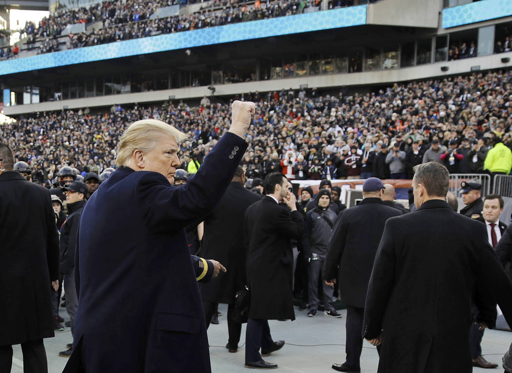 President Donald Trump gestures as he walks to his seat ahead of an NCAA college football game between Army and Navy, Saturday, Dec. 8, 2018, in Philadelphia. (AP Photo/Matt Rourke)