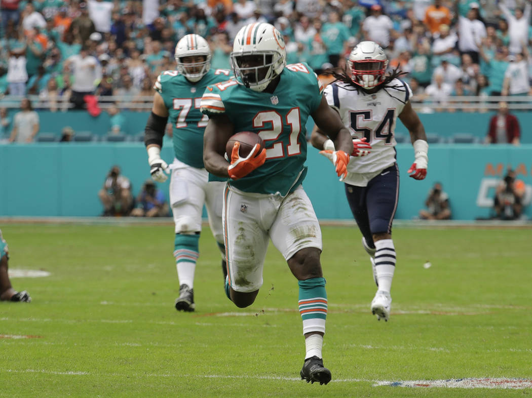Miami Dolphins running back Frank Gore (21) runs the ball, during the first half of an NFL football game against the New England Patriots, Sunday, Dec. 9, 2018, in Miami Gardens, Fla. (AP Photo/Ly ...