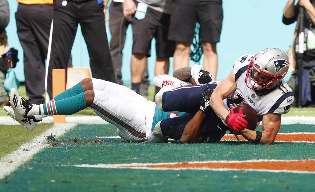 New England Patriots wide receiver Julian Edelman (11) catches a touchdown pass, during the first half of an NFL football game against the Miami Dolphins, Sunday, Dec. 9, 2018, in Miami Gardens, F ...