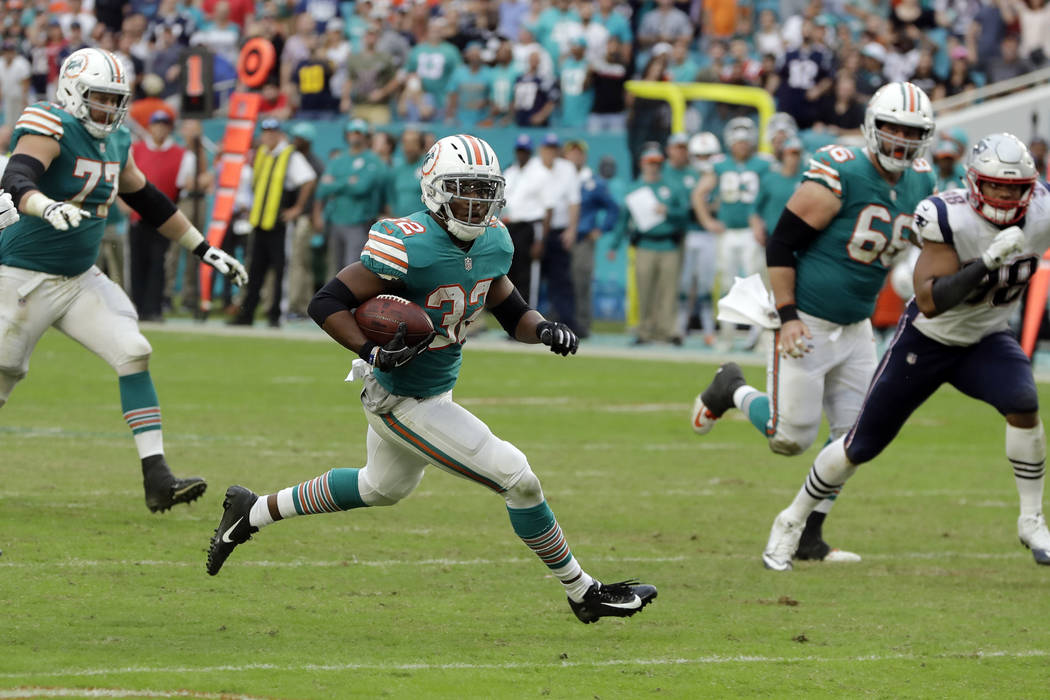 Miami Dolphins running back Kenyan Drake (32) runs for a touchdown, during the second half of an NFL football game against the New England Patriots, Sunday, Dec. 9, 2018, in Miami Gardens, Fla. (A ...