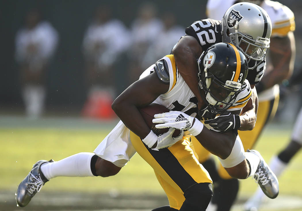 Pittsburgh Steelers wide receiver James Washington (13) is tackled by Oakland Raiders defensive back Rashaan Melvin (22) during the first half of an NFL football game in Oakland, Calif., Sunday, D ...