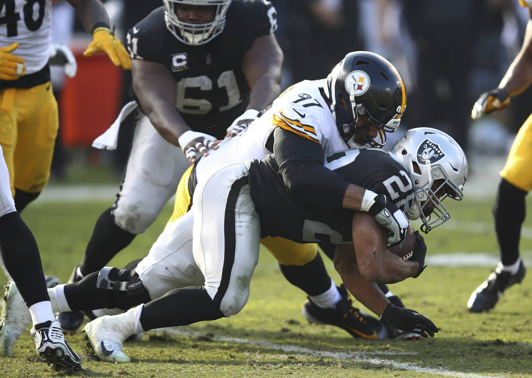 Pittsburgh Steelers defensive end Cameron Heyward (97) tackles Oakland Raiders running back Doug Martin (28) during the first half of an NFL football game in Oakland, Calif., Sunday, Dec. 9, 2018. ...