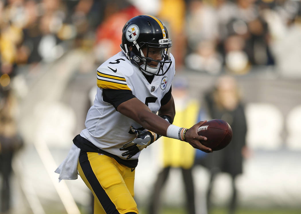 Pittsburgh Steelers quarterback Joshua Dobbs (5) hands offn against the Oakland Raiders during the second half of an NFL football game in Oakland, Calif., Sunday, Dec. 9, 2018. (AP Photo/D. Ross C ...
