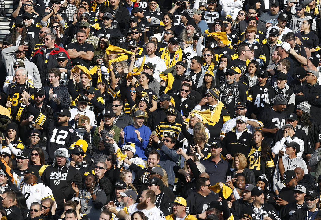 Fans cheer during the first half of an NFL football game between the Oakland Raiders and the Pittsburgh Steelers in Oakland, Calif., Sunday, Dec. 9, 2018. (AP Photo/D. Ross Cameron)