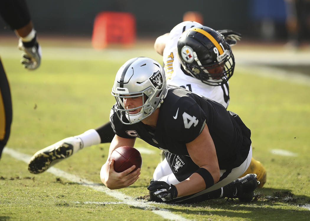 Oakland Raiders quarterback Derek Carr (4) is sacked by Pittsburgh Steelers defensive end Stephon Tuitt, rear, during the first half of an NFL football game in Oakland, Calif., Sunday, Dec. 9, 201 ...