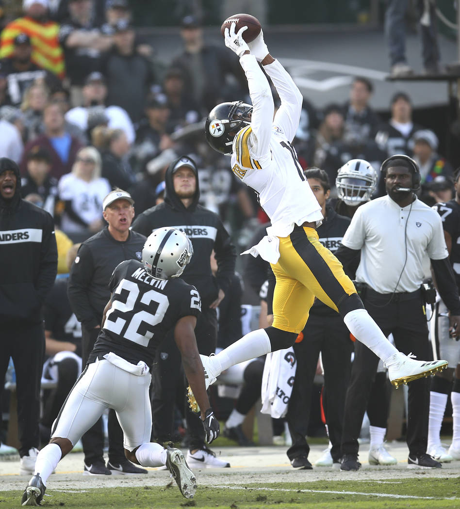 Pittsburgh Steelers wide receiver JuJu Smith-Schuster, top, catches a pass over Oakland Raiders defensive back Rashaan Melvin (22) during the first half of an NFL football game in Oakland, Calif., ...