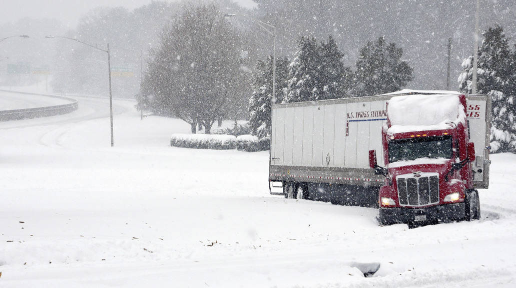 A tractor trailer is stuck on an off ramp from Business I-40 on to Stratford Road, US 158, as snow falls Sunday morning, Dec. 9, 2018 in Winston-Salem, N.C. (Walt Unks/Winston-Salem Journal via AP)
