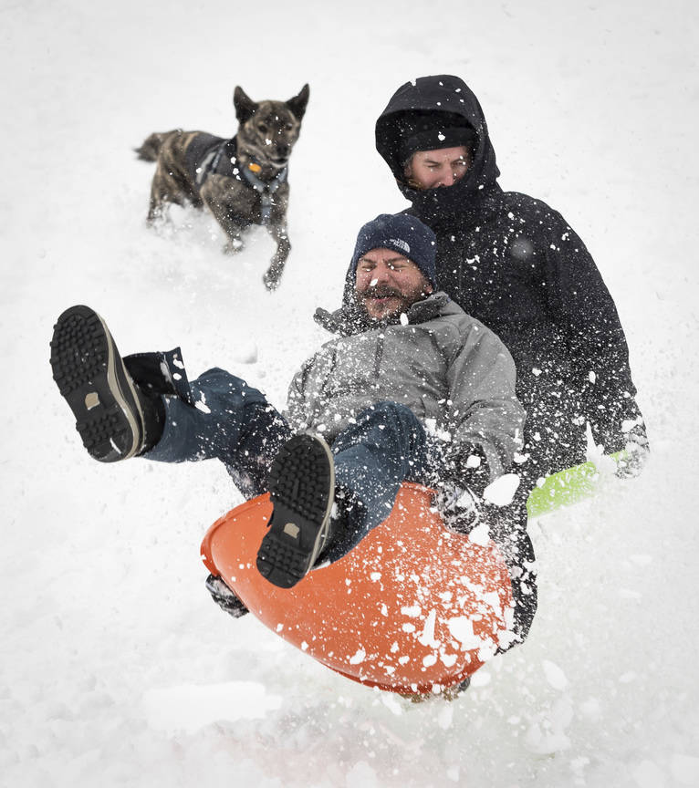 Zac Evans, front, and Stephen LaFleur go airborn sledding off a ramp while Deac, the dog, follows them down the hill at Ardmore Park Soccer Field on Sunday, Dec. 9, 2018, in Winston-Salem, N.C. (A ...
