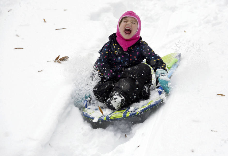 Ella Gold, 5, screams as she sleds down a hill at Temple Emanuel, Sunday morning, Dec. 9, 2018 in Winston-Salem, N.C. (Walt Unks/Winston-Salem Journal via AP) (Walt Unks/Winston-Salem Journal via AP)