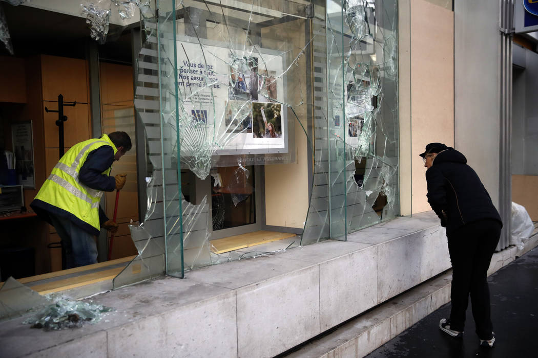 A worker clears debris in a bank as a man watches through smashed windows, in Paris, Sunday, Dec. 9, 2018. Paris monuments reopened, cleanup workers cleared debris and shop owners tried to put the ...