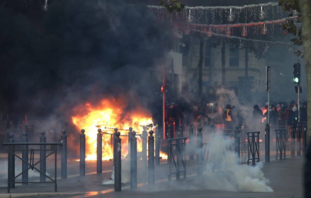 Demonstrators stand behind a burning car during clashes, Saturday, Dec. 8, 2018 in Marseille, southern France. French riot police fired tear gas and water cannon in Paris on Saturday, trying to st ...